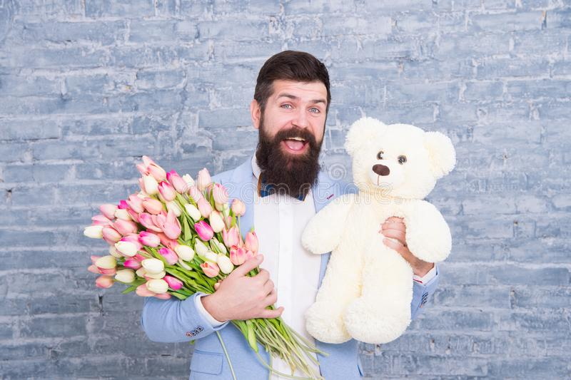 I am sorry. Womens day. Love you so much. March 8. Spring gift. Bearded man hipster with flowers. Bearded man with tulip royalty free stock photo