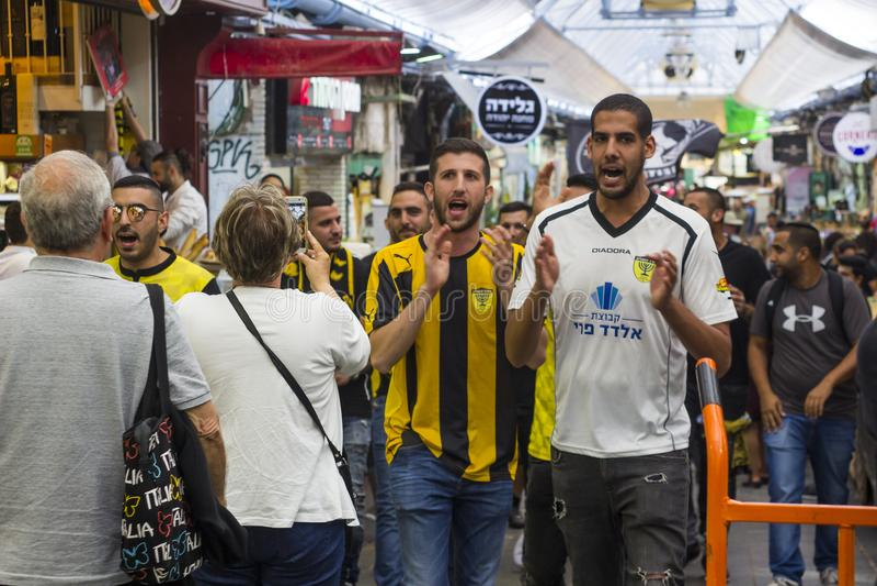 I sostenitori di calcio nella striscia di Beitar Jerusalem marciano giù il centro commerciale del mercato coperto Yehuda di Mahan fotografia stock libera da diritti
