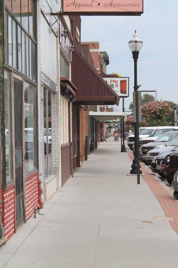 I stadens centrum Fremont, Nebraska, trottoar med shoppar och tecken och bilar arkivfoto