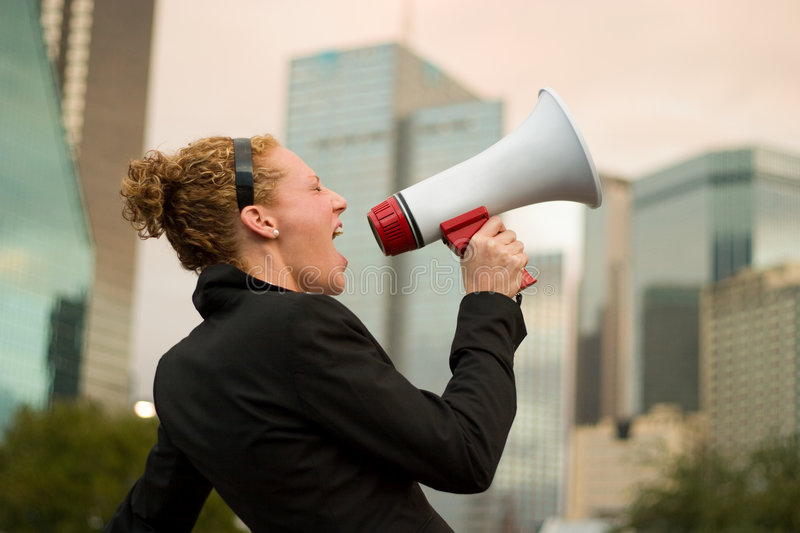 Am I Still Making Myself Clear. Young business woman making herself heard with a megaphone stock photos