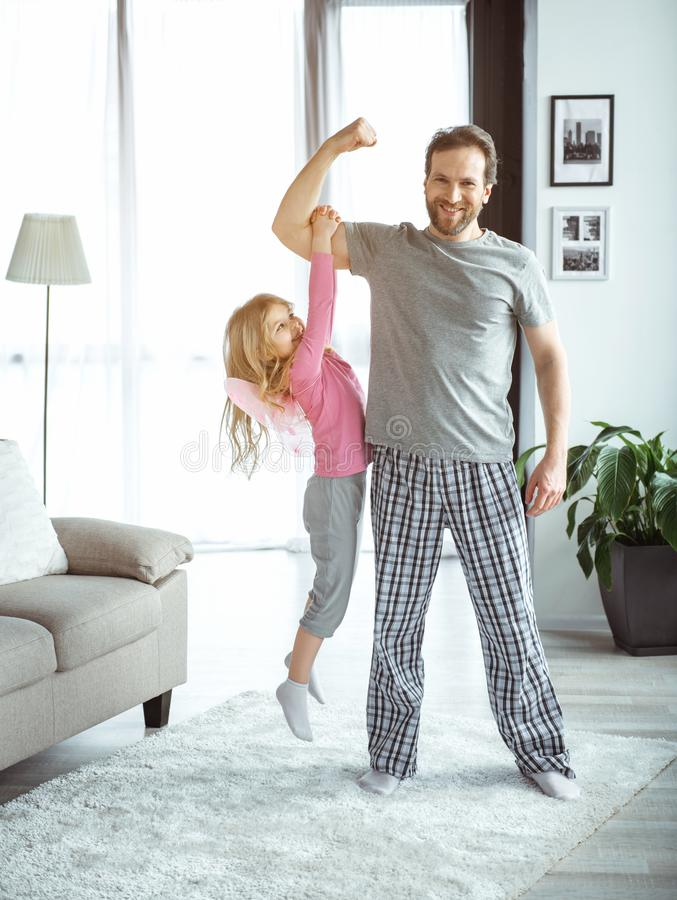 Carefree father and daughter playing at home. I am so strong. Full length portrait of confident men is holding his little child on his arm muscle. He is looking royalty free stock photos