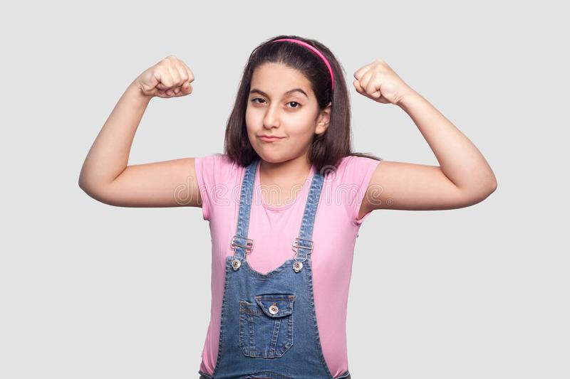 I am strong. Portrait of satisfied brunette young girl in casual pink t-shirt and blue overalls standing with raised arms and. Looking at camera. indoor studio royalty free stock photo