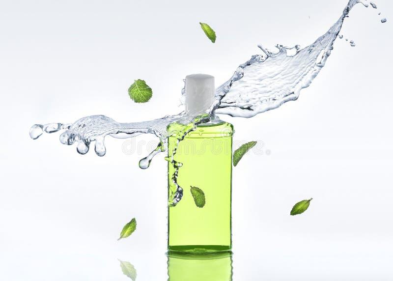 I supporti d'idratazione di erbe dello sciampo sui precedenti bianchi con le foglie della spruzzata e di menta dell'acqua immagini stock