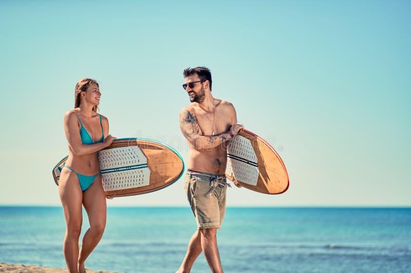 I surfisti della donna e dell'uomo che camminano sulla spiaggia Vacation Spo estremo fotografia stock libera da diritti