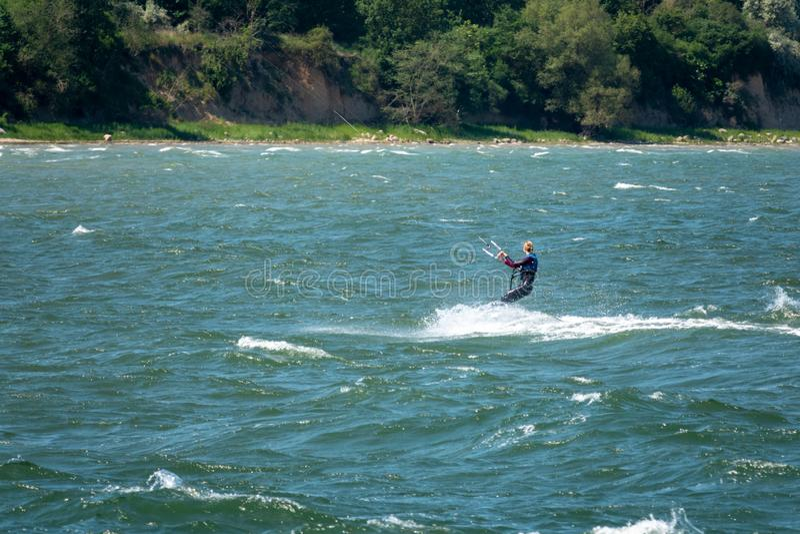 I surfisti di un aquilone corrono attraverso il mare fotografia stock