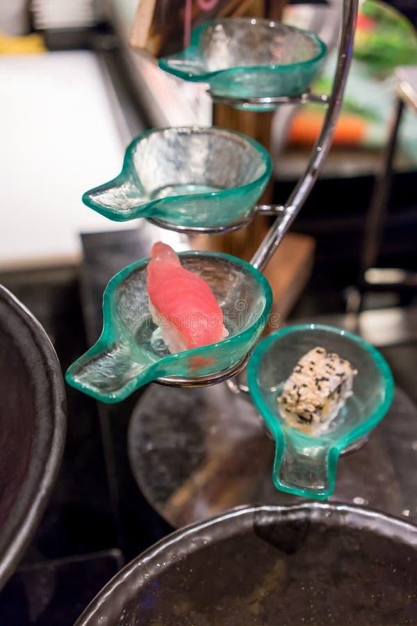 I sushi alti chiusi del tonno in cucchiaio di vetro hanno modellato la ciotola che dispone sul candl immagine stock