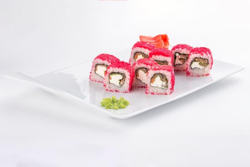 I sushi rotolano con il formaggio di color salmone, dell'avocado, cremoso e l'alimento giapponese di tobiko isolati su fondo bian fotografia stock