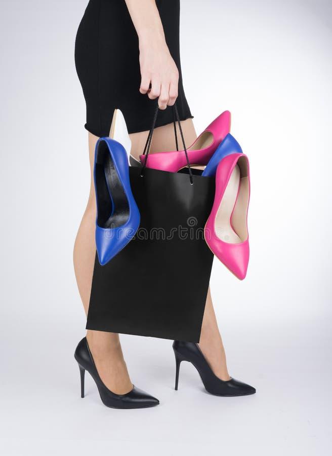 i svart klänning med shoppingpåsen mycket av skor i hennes händer royaltyfri foto