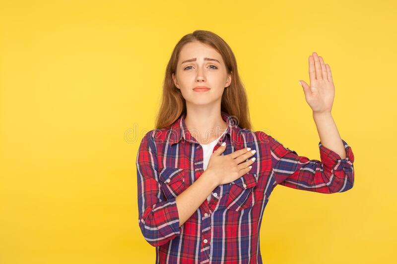 I swear, promise! Portrait of sincere honest ginger girl in shirt holding hand up and on chest, pledging allegiance, taking oath. With responsible expression stock photo