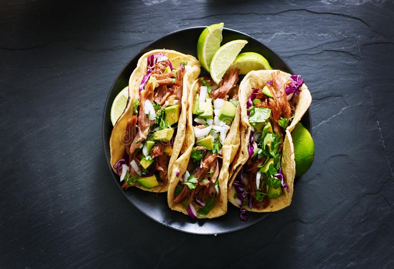 I taci messicani della via pongono pianamente la composizione con i carnitas della carne di maiale, l'avocado, la cipolla, il cor immagini stock