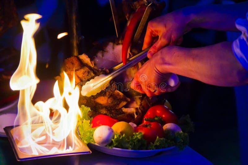 I tagli del cuoco unico arrostiscono la carne con un coltello, servito con le fiamme di fuoco, foto dell'alimento del ristorante immagini stock