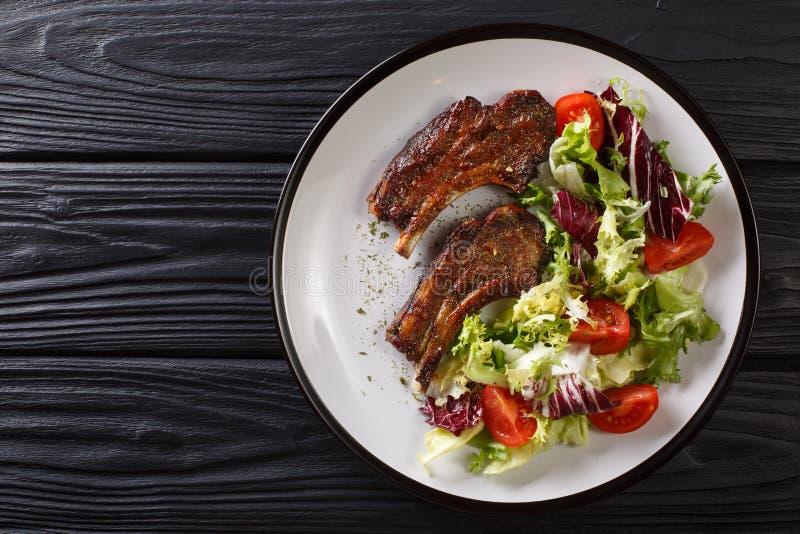 I tagli di agnello fritti deliziosi sono servito con il primo piano dell'insalata di verdura fresca su un piatto vista superiore  fotografia stock