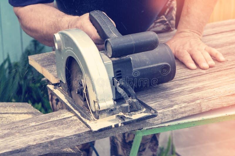 I tagli maschii della mano con una circolare hanno visto un pezzo di bordo un giorno soleggiato, primo piano modificato immagini stock libere da diritti