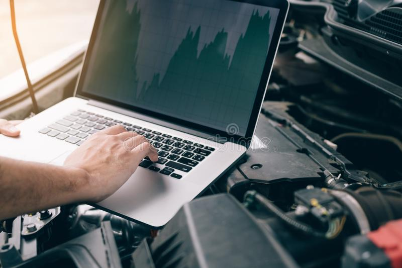 I tecnici delle riparazioni dell'automobile utilizzano i computer portatili per misurare i valori del motore per l'analisi fotografia stock