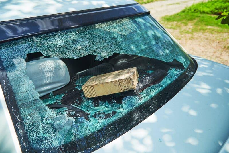 I teppisti hanno gettato un mattone nella macchina ed hanno rotto il vetro fotografia stock