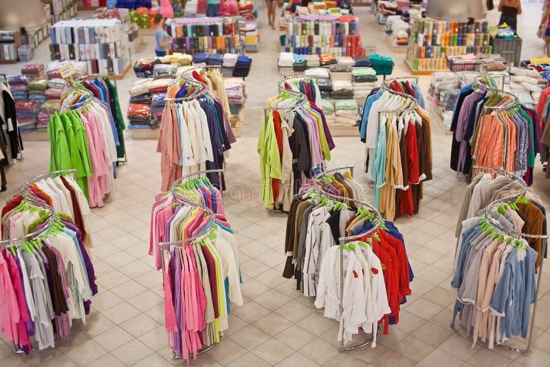 I tessuti domestici del negozio con i ganci che appendono hanno colorato gli accappatoi immagini stock