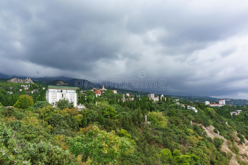 I tetti delle case sono veduti fra i pini ed i cipressi sul pendio delle montagne della Crimea nel villaggio Simeiz della localit immagini stock