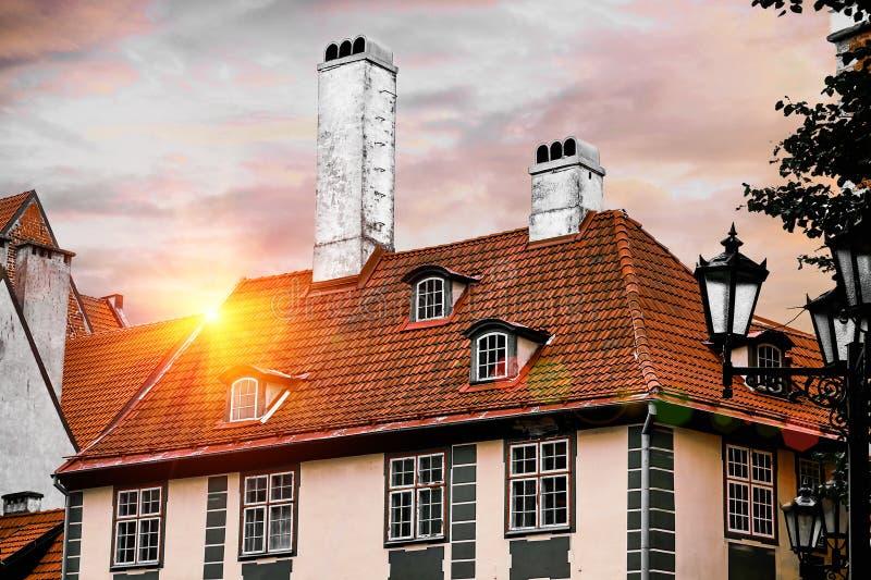 I tetti di vecchie case in via di iela di Skarnu a Riga, Lettonia contro cielo blu con la lente impressionante si svasa fotografie stock libere da diritti