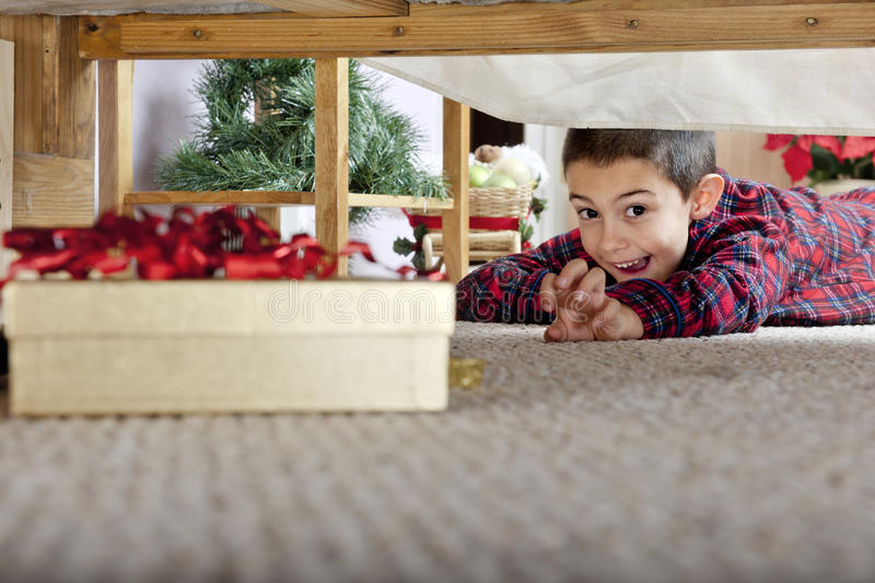 I Think I Got It!. A young elementary boy delighted at seeing a boxed gift under his parents' bed royalty free stock image