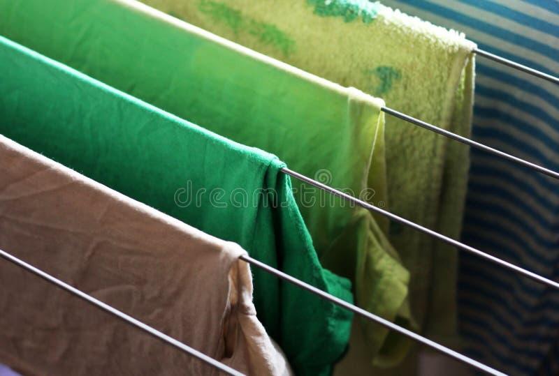 I tipi differenti di vestiti hanno lasciato l'attaccatura da asciugarsi fotografia stock