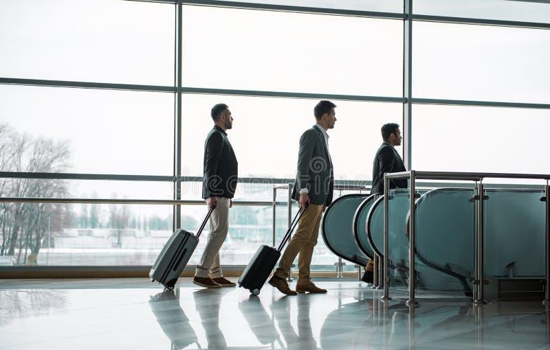 I tipi piacevoli stanno camminando con bagagli alla scala mobile fotografie stock