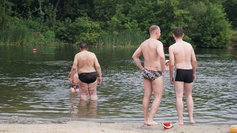 I tipi si rilassano sulla spiaggia che sta sulla riva immagine stock libera da diritti
