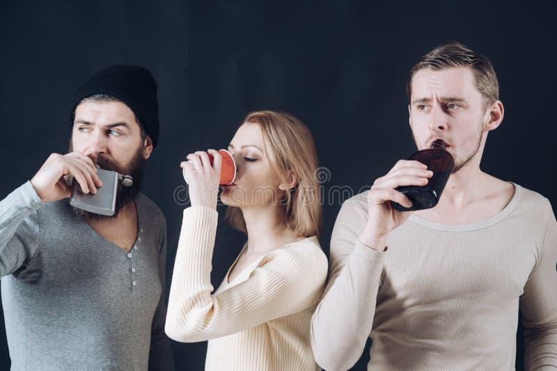 I tipi tengono la tazza, boccetta con l'alcool, bevanda La società degli amici calmi spende lo svago con le bevande Alcool, amici fotografia stock