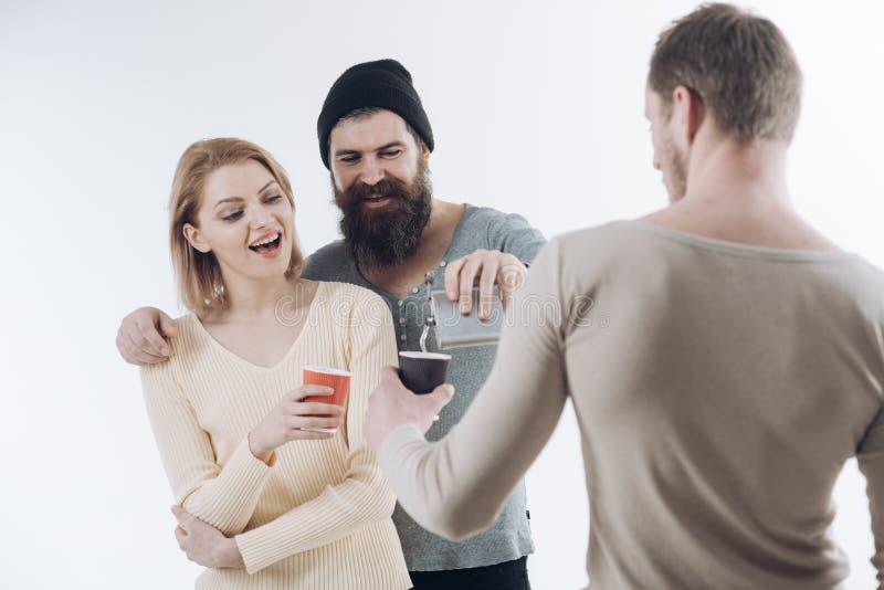 I tipi tengono la tazza, boccetta con l'alcool, parlano La società degli amici allegri spende lo svago con le bevande Concetto di fotografia stock