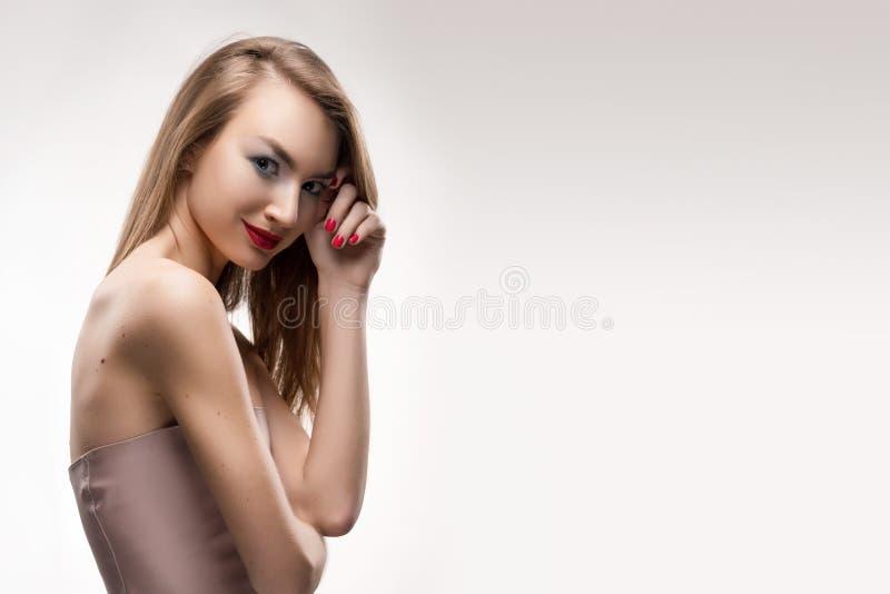 I tocchi sorridenti della ragazza delle belle labbra rosse bionde dalle dita fa fotografie stock