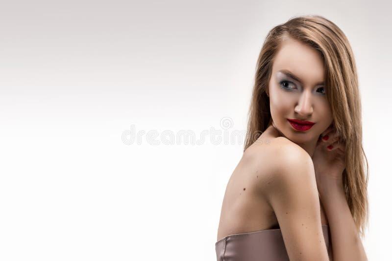 I tocchi sorridenti della ragazza delle belle labbra rosse bionde dalle dita fa immagine stock libera da diritti