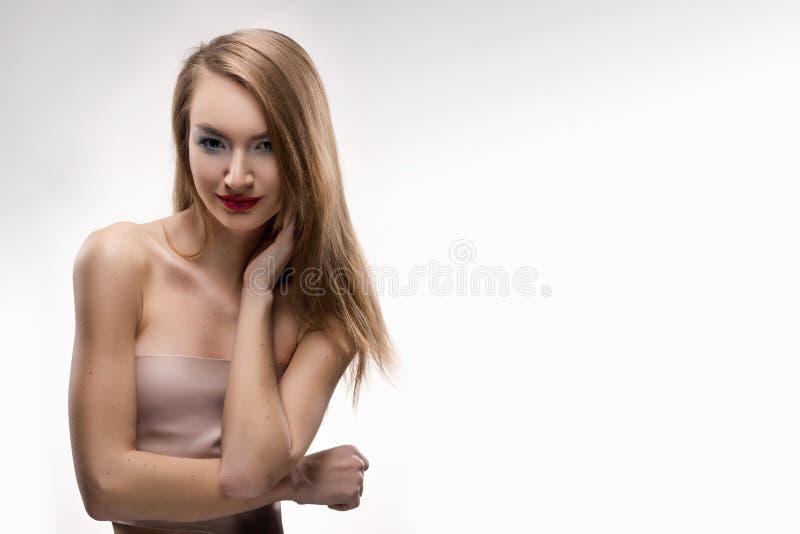 I tocchi sorridenti della ragazza delle belle labbra rosse bionde dalle dita fa immagini stock libere da diritti