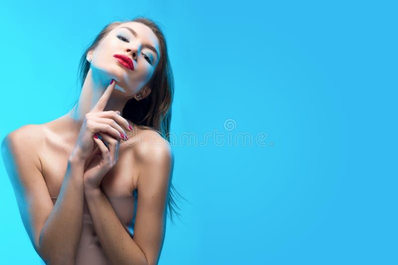 I tocchi sorridenti della ragazza delle belle labbra rosse bionde dalle dita fa immagini stock