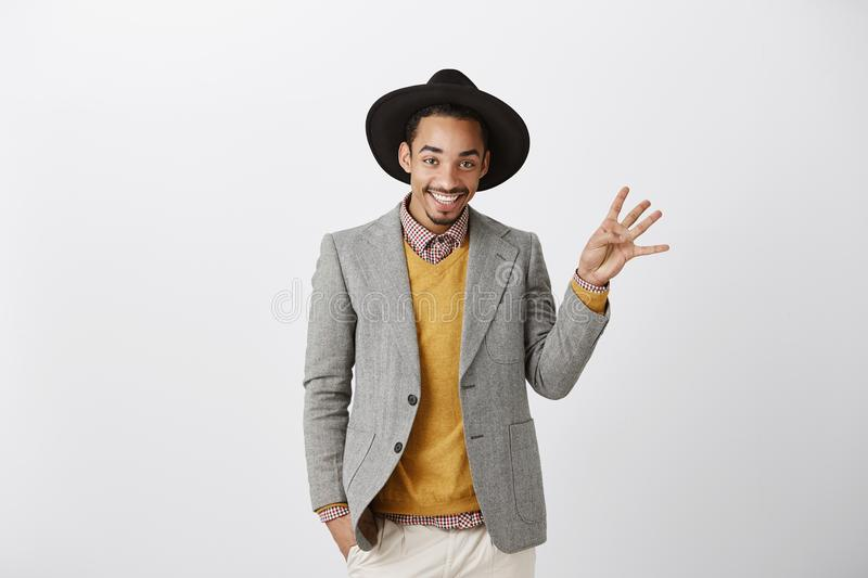 I took four phone numbers during party. Satisfied handsome african-american in stylish hat and fashionable outfit stock photos