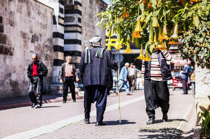 An ordinary day and local people are on the street. I took this photo in Adana, Turkey. this street is near the Adana Ulu mosque. Some people with local clothes royalty free stock images
