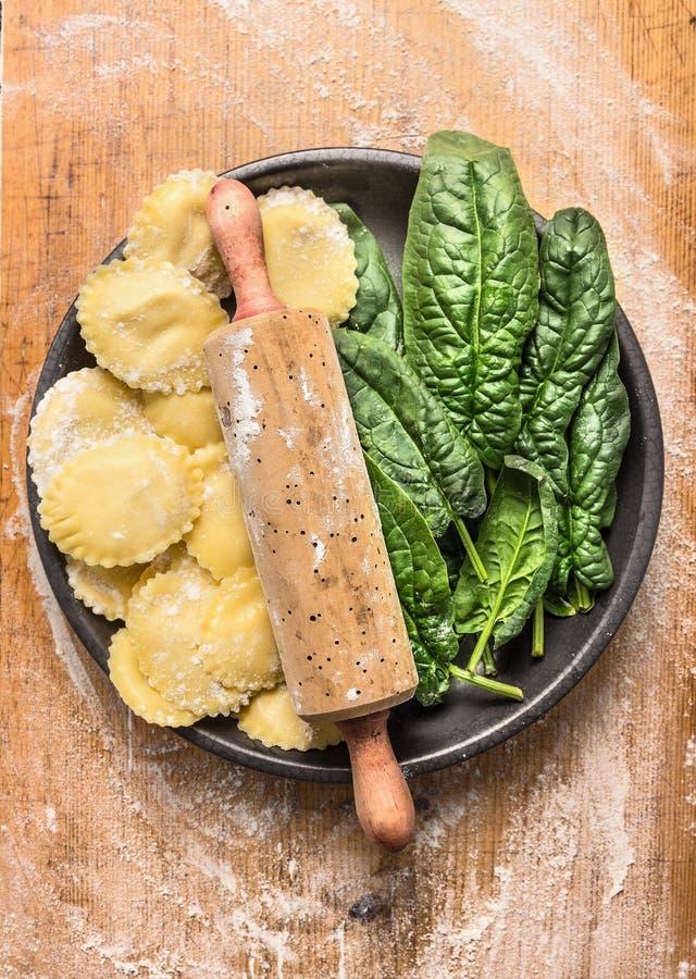 I tortellini crudi con il matterello e gli spinaci freschi lasciano in piatto grigio su fondo di legno con la farina di frumento immagini stock