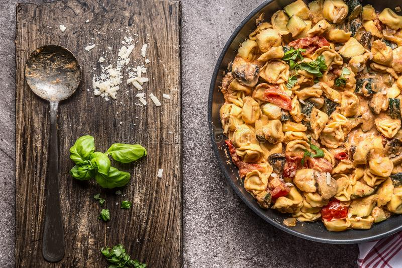 I tortellini serviscono con le verdure sauce e cucchiai, vista superiore Vegetariano in buona salute che cucina e che mangia Alim fotografie stock