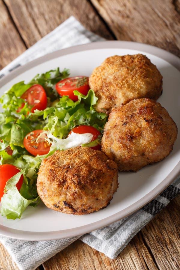 I tortini impanati danesi Karbonader della carne di maiale sono servito con insalata fresca c fotografie stock libere da diritti