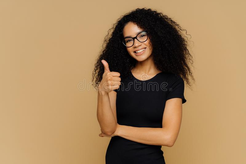 I totally agree. Good looking satisfied Afro American woman keeps thumb up, dressed in casual black t shirt, has crisp hair, wears royalty free stock image