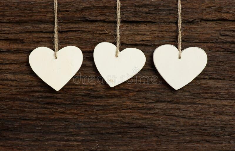 I tre cuori del biglietto di S. Valentino bianco di amore che appendono sulle sedere di legno di struttura immagini stock