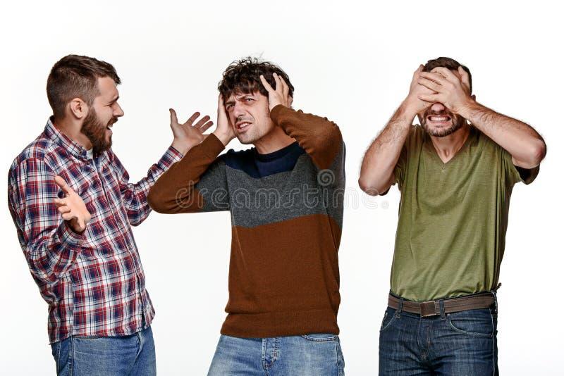 I tre uomini che guardano con differenti emozioni fotografia stock