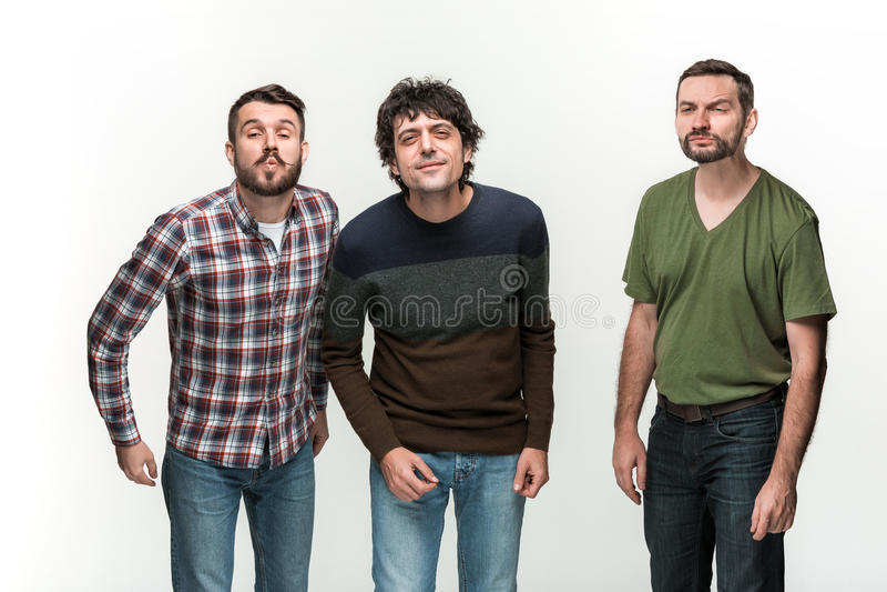 I tre uomini sono sorridere, esaminante la macchina fotografica fotografie stock libere da diritti