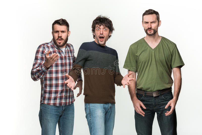 I tre uomini sono sorridere, esaminante la macchina fotografica immagini stock