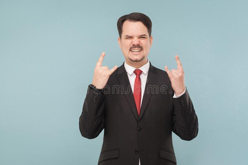 Businessman showing rock and roll sign stock photo