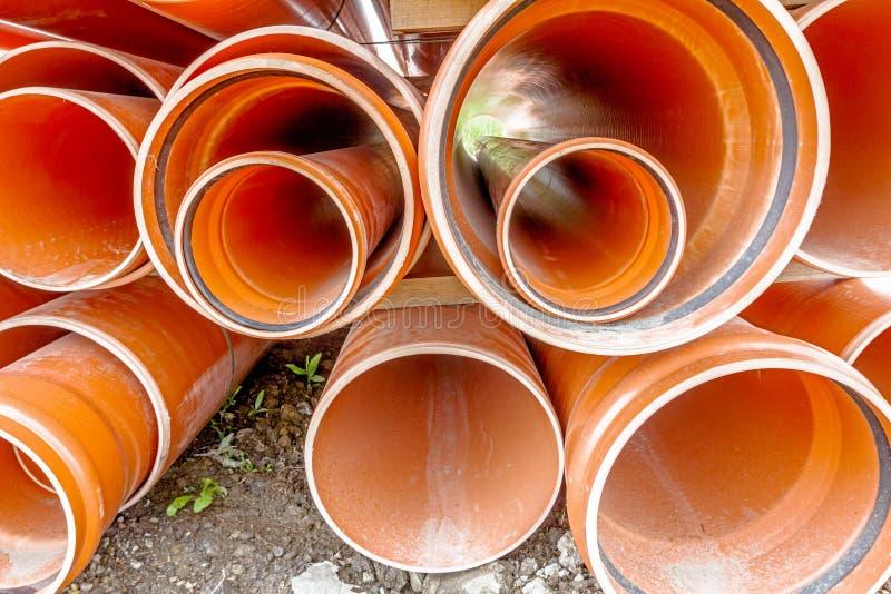 I tubi arancio del PVC, tubi sono impilati in un mucchio al cantiere, fotografia stock libera da diritti