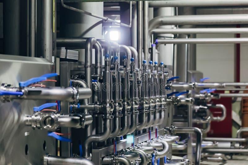 I tubi industriali dell'acciaio inossidabile si sono collegati con i tini e le valvole di regolazione fotografia stock