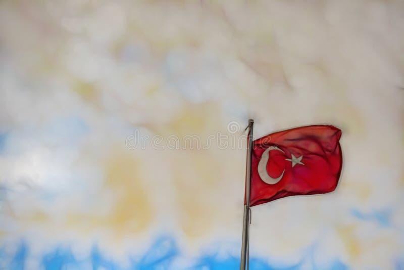 I turco diminuiscono sull'asta della bandiera ed inbandierano l'onda immagine stock