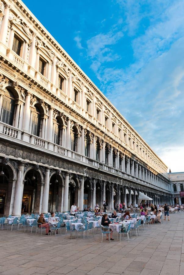 I turisti al quadrato di San Marco hanno un resto in uno di molti caffè fotografia stock