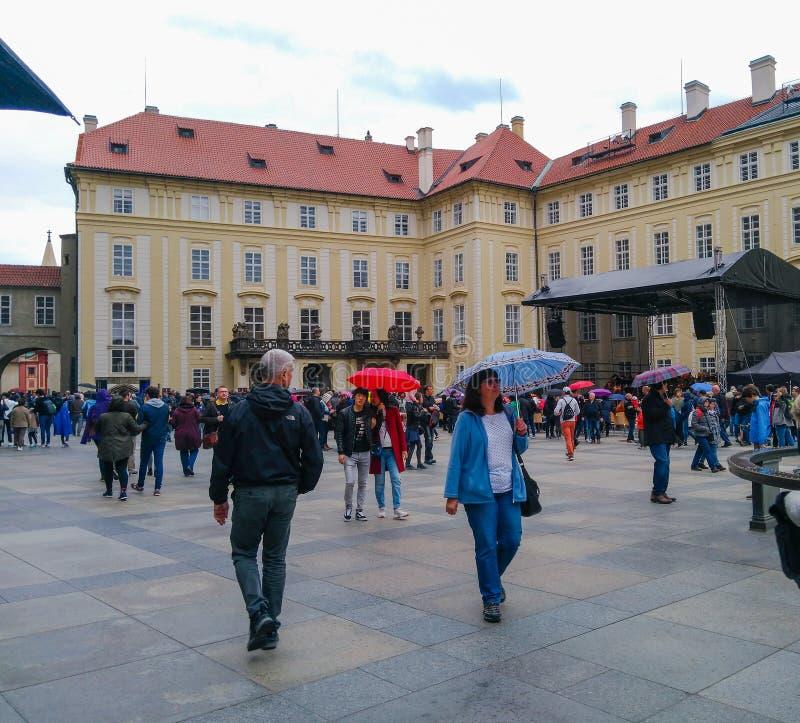 I turisti camminano con gli ombrelli nel castello di Praga in tempo piovoso fotografia stock