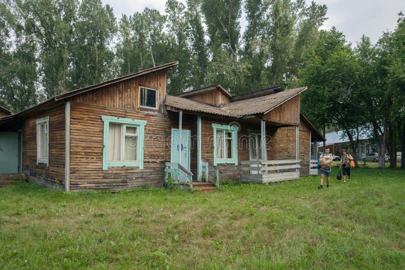 I turisti camminano dopo la casetta turistica dell'estate di legno al campeggio di Iskra nel villaggio di Shushenskoye fotografia stock libera da diritti