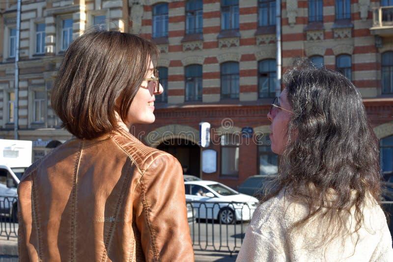 I turisti delle giovani signore nel supporto di San Pietroburgo Russia su un ponte all'costruzioni gialle quadrano e guardano i d fotografia stock